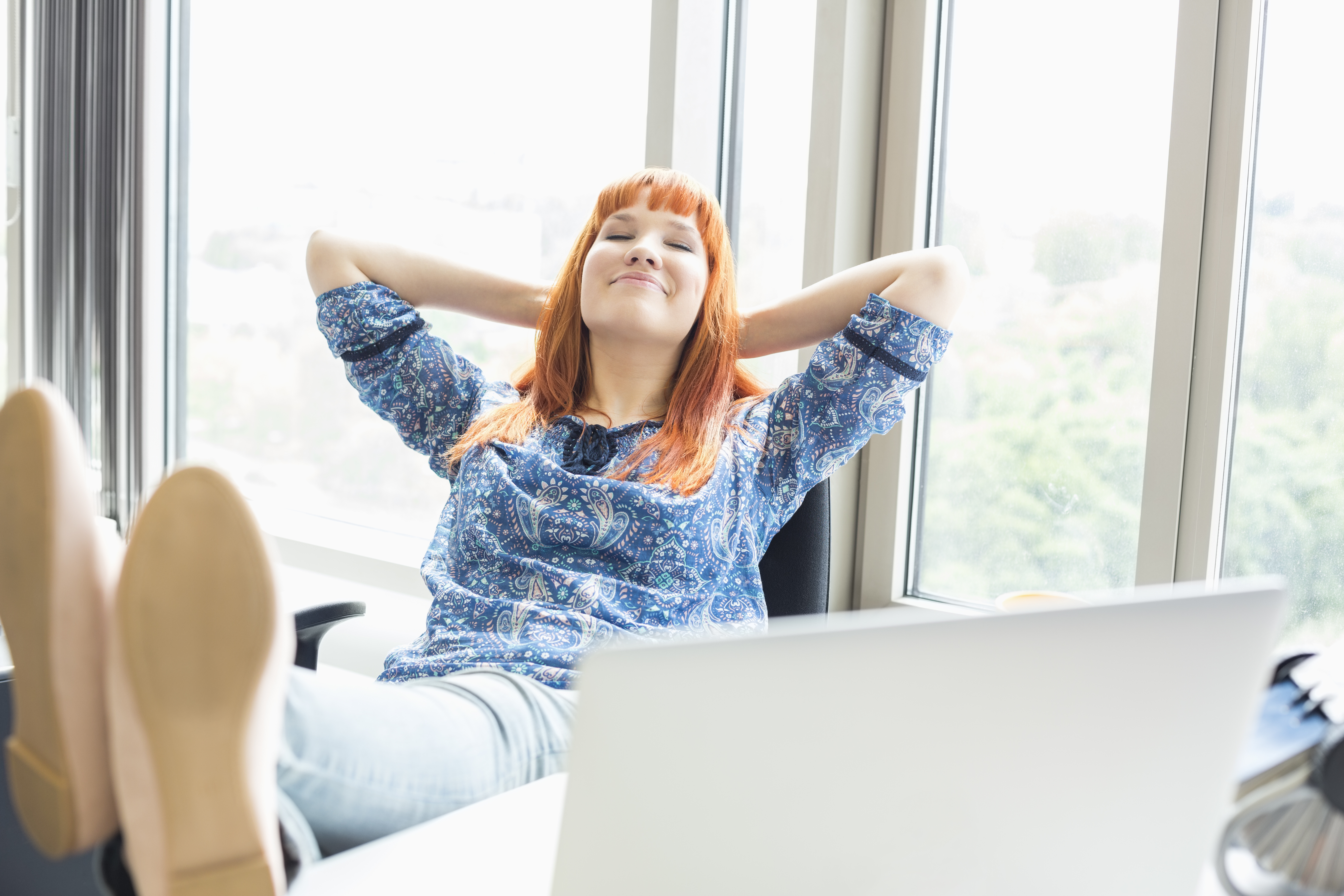 Businesswoman relaxing with feet up at desk in creative office